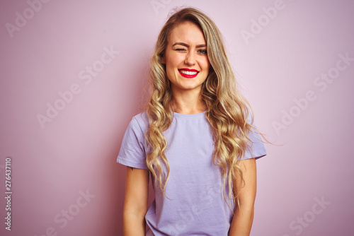 Photo  Young beautiful woman wearing purple t-shirt standing over pink isolated background winking looking at the camera with sexy expression, cheerful and happy face
