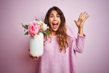 Young Beautiful Woman Holding A Pot Of Flowers Over Pink Isolated Background Very Happy And Excited, Winner Expression Celebrating Victory Screaming With Big Smile And Raised Hands