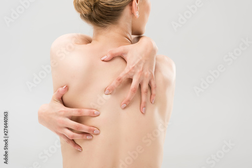 plakat back view of sexy naked woman embracing herself isolated on grey