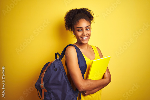 American student woman wearing backpack holding notebook over isolated yellow ba Canvas Print
