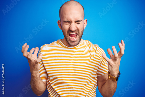 Kiev Young bald man with beard wearing casual t-shirt over blue isolated background celebrating mad and crazy for success with arms raised and closed eyes screaming excited. Winner concept