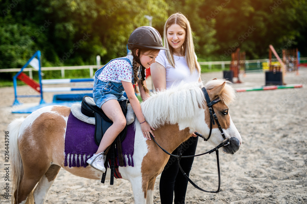 Fototapety, obrazy: Cute little girl and her older sister enjoying with pony horse outdoors at ranch.