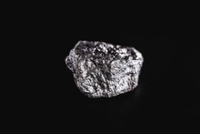 Big Silver Nugget On Black Background. Raw Silver Stone, Native Silver Nugget From Liberia, Isolated On Black Background. Mineral Extraction.