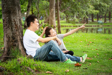 Happy Asian Adult Man And Cute Child Girl With Love,hugging And Smiling,hand Of Father Caress His Hair Little Daughter In Outdoor Park,sitting Under The Tree In Nature,father's Day,family,love Concept