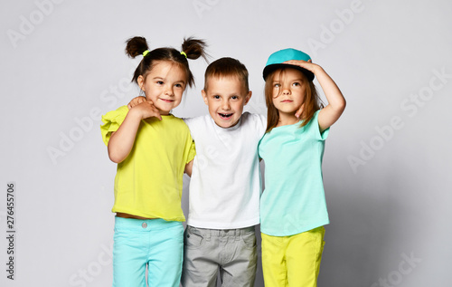 Full Body Shot Of Three Children In Bright Clothes Two Girls And
