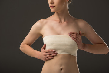 partial view of woman with breast bandage isolated on grey