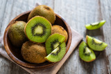 Fresh kiwi fruit in the bowl on wooden background