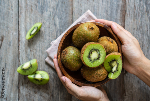 Obraz na plátně Fresh kiwi fruit in the bowl on wooden background