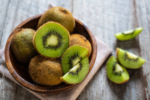 Fresh kiwi fruit in the bowl on wooden background - 276457532