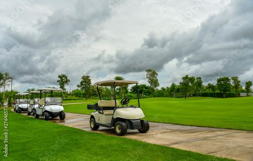 Golf carts parking near golf course with golfers and caddie are in competition,blue cloud sky background - 276465734