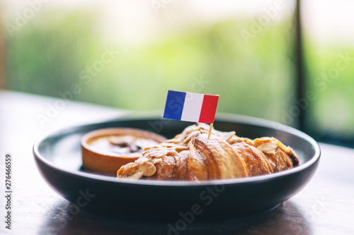 Photo A piece of croissant and tart with a flag of France in a black plate on wooden t