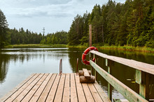 Lifebuoy On A Pier Of A Forest Lake On A Cloudy Day In Summer