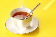 Morning Sun Shines To White Porcelain Cup With Hot Black Tea, Just Brewed, Silver Spoon In, On Yellow Board