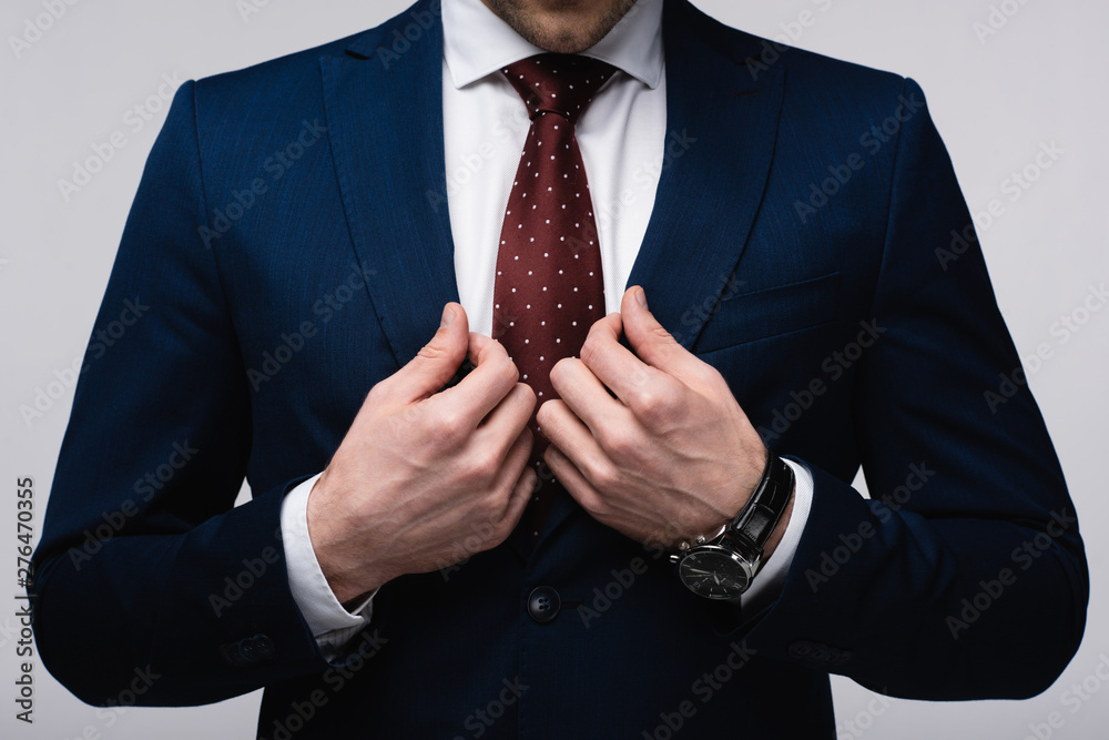 Fototapety, obrazy: cropped view of confident businessman touching suit isolated on grey