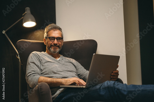 Fotografie, Obraz  middle aged man using laptop sitting in sofa at his home