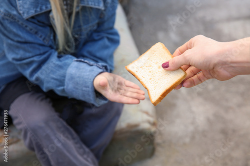 Fotografija  Woman giving food to homeless little girl outdoors