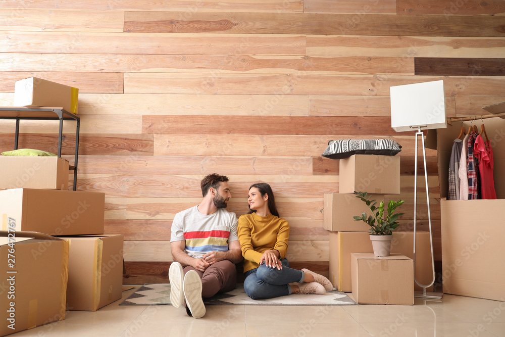 Fototapeta Young couple with belongings after moving into new house