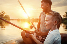 Happy Father And Son Together Fishing From A Boat At Sunset Time