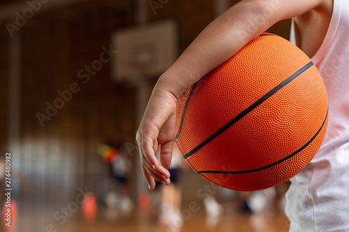 Schoolboy with basketball standing in basketball court