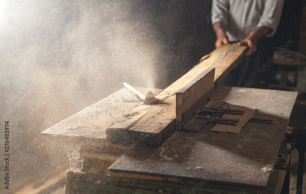 Fototapety, obrazy: Carpenter cutting a wooden plank with a carpentry machine.