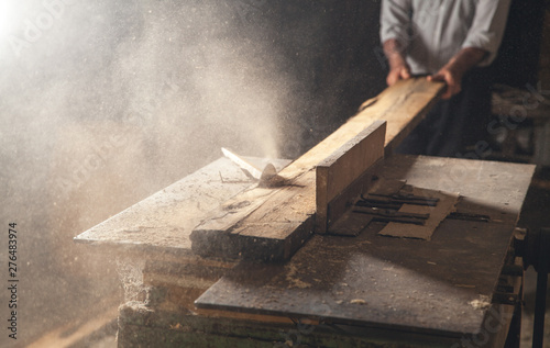 Carpenter cutting a wooden plank with a carpentry machine.