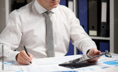Montage in der Fensternische Logo Businessman working with tablet pc, calculating, reading and writing reports. Office employee, table closeup. Business financial accounting concept.