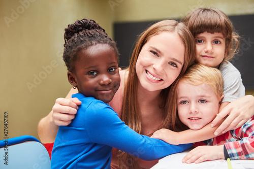 Children hug their kindergarten teacher