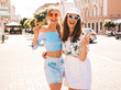 Two young beautiful smiling hipster girls in trendy summer clothes and panama hat. Sexy carefree women posing on street background.Positive models having fun in sunglasses.Shows peace sign