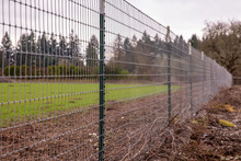 A Welded Wire Mesh Fence On A Border Of A Farm Along A Gravel Walkway