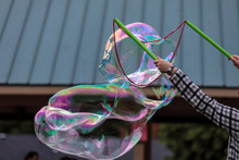 A Hands Holding Two Bubble Wands Making Giant Colorful Bubbles