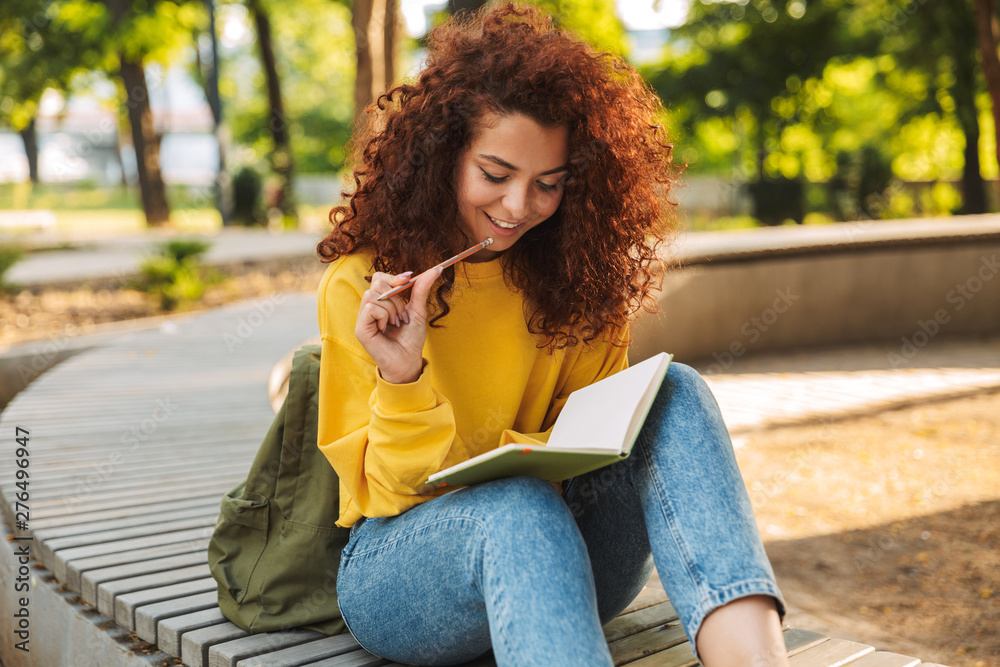 Fototapety, obrazy: Young beautiful curly student girl sitting outdoors in nature park writing notes in notebook.