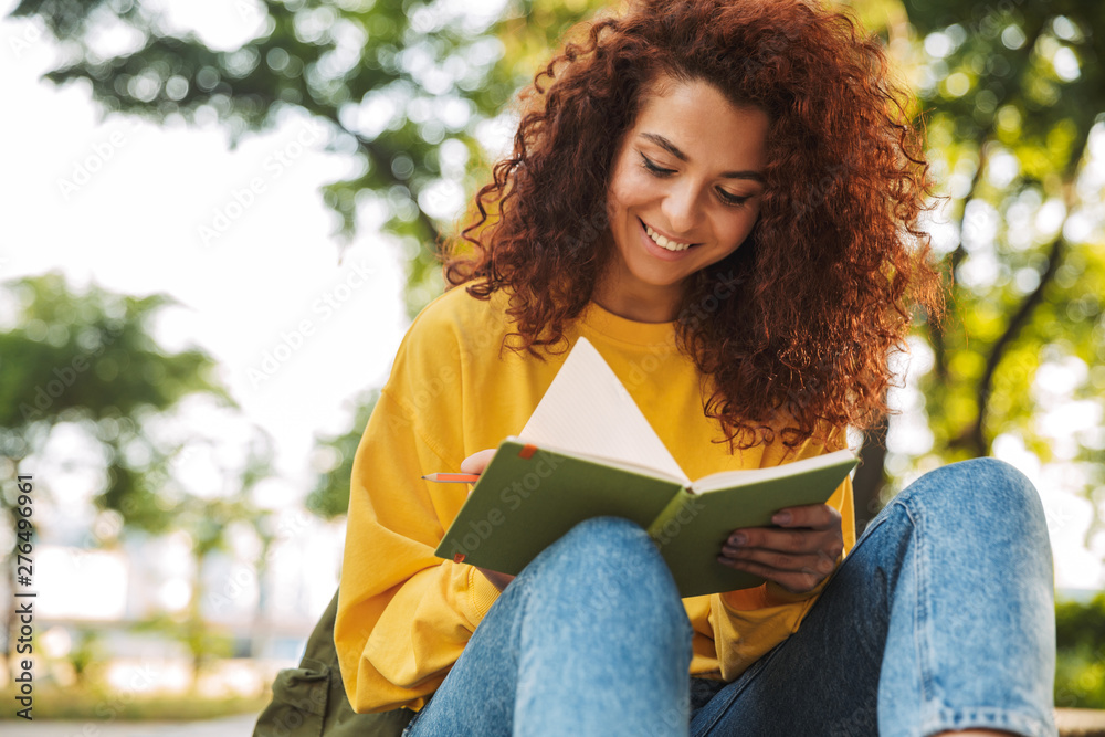 Fototapeta Young beautiful curly student girl sitting outdoors in nature park writing notes in notebook.