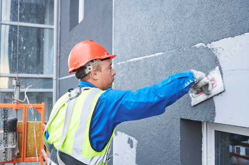 Canvas Print Facade worker plastering external wall of building