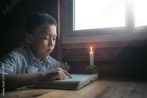 Photo  Boy reading bible on wooden table near the window. focus at face.