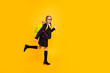 Full size photo of active kid moving walking isolated looking isolated over yellow background