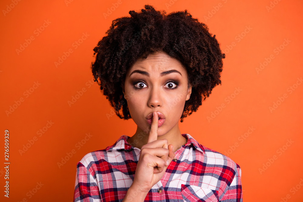 Fototapeta Close-up portrait of her she nice attractive lovely scared nervous wavy-haired lady in checked shirt showing shh sign censorship isolated on bright vivid shine orange background