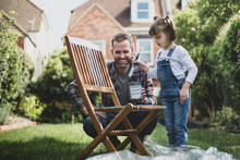 Father And Daughter Painting Garden Furniture Together