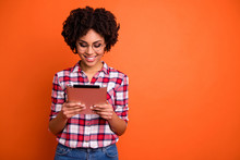 Portrait Of Nice Cute Attractive Cheerful Cheery Smart Clever Intellectual Wavy-haired Lady Nerd Wearing Checked Shirt Reading Digital E-book Isolated Over Bright Vivid Shine Orange Background