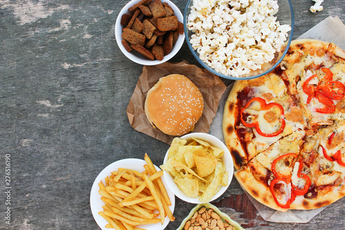 Fast food on old wooden background. Concept of junk eating. Top view. Flat lay. © Victoria М