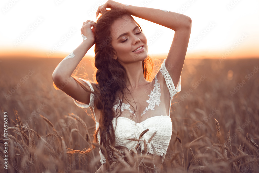 Fototapeta Boho chic style. Portrait of bohemian girl with white art posing over wheat field enjoying at sunset. Outdoors photo. Tranquility concept. Lifestyle.