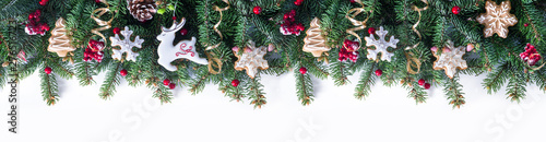 Fototapeta Festive Christmas border - green fir branches decorated with ginger Christmas glazed cookies in form of reindeer and snowflakes, red berries, banner format,  isolated on white. obraz