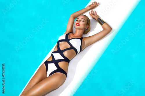 Fototapeta Elegant sexy woman in luxury bikini on the sun-tanned slim and shapely body is posing near the swimming pool. Sunbathing By Swimming Pool On Travel . Beauty, Wellness, Lifestyle - Image obraz na płótnie