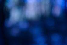 Navy Blue Bokeh Lights. Defocused Lens Flare Effect. Dark Abstract Art Background.