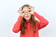 Making Face,funny  Foolishes Portrait Of Beautiful Child Girl Do Binoculars With Tongue Out ,against White Background.