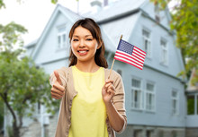 Independence Day, Mortgage And Real Estate Concept - Happy Asian Young Woman With American Flag Over House Background