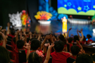 Children excitingly raise hands watching the performance in the theater