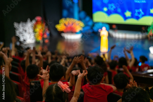 Fotografía  Children excitingly raise hands watching the performance in the theater