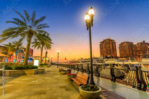Fényképezés  Marina corniche promenade at night in Porto Arabia at the Pearl-Qatar, Doha, with residential towers and luxury boats and yachts in Persian Gulf, Middle East