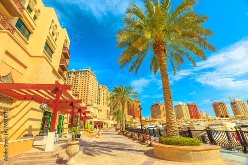 Fényképezés  Palm trees along luxury marina corniche walkway promenade in Porto Arabia at the Pearl-Qatar, Doha