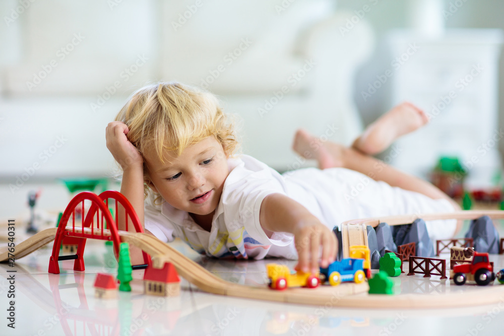 Fototapety, obrazy: Kids play wooden railway. Child with toy train.